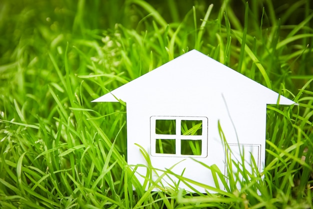 O conceito ou papel branco da casa conceitual em sua mão em uma grama verde de verão em um fundo, um símbolo para a construção, meio ambiente, crédito, propriedade ou casa