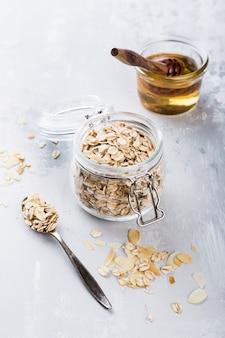 O conceito saudável do café da manhã, aveia lasca-se no frasco de vidro com mel.