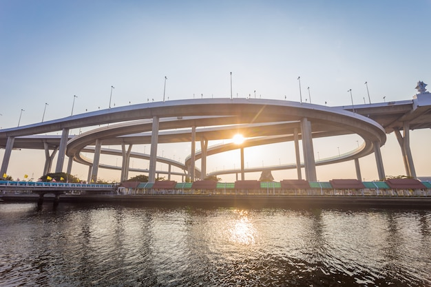 O concreto moderno constrói uma ponte sobre as maneiras através do rio grande no tempo do por do sol com luz solar.