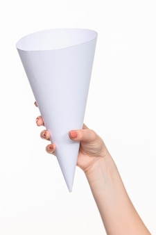 O cone nas mãos femininas no espaço em branco