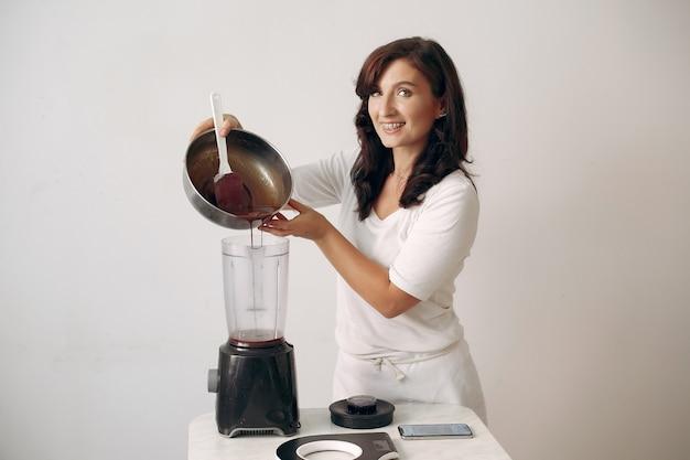 O confeiteiro mistura os ingredientes. a senhora está preparando a sobremesa. a mulher faz um bolo.