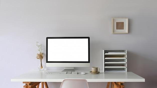 O confortável monitor de computador da área de trabalho está sobre uma mesa de trabalho branca, cercada por equipamentos de escritório.