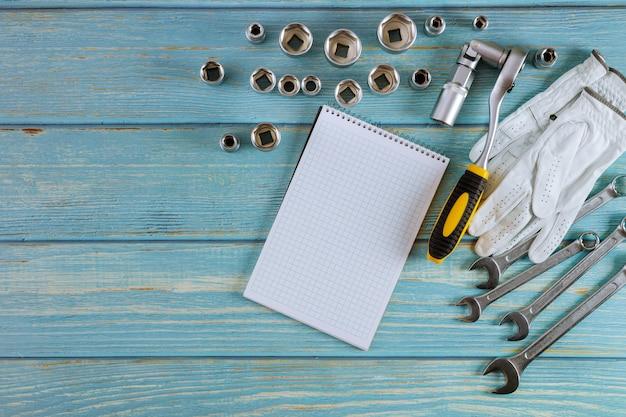 O conjunto de ferramentas automotivo profissional de chaves cromo ferramentas com as luvas protetoras do bloco de notas em espiral no fundo de madeira.