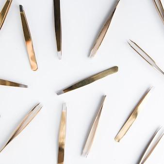 O conjunto de ferramentas de um cosmetologista pinça em um fundo branco ferramenta em um estojo de couro preto