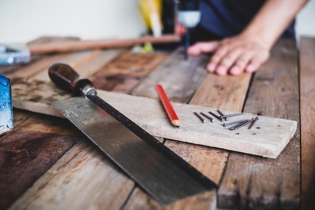 O conjunto de ferramentas trabalha pregos, lápis e viu na tabela de madeira.