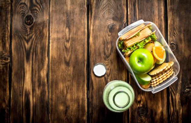 O conjunto de piquenique. sanduíches com queijo e bacon, frutas e milkshake.