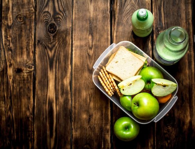 O conjunto de piquenique. sanduíches, frutas e um milk-shake de kiwi.