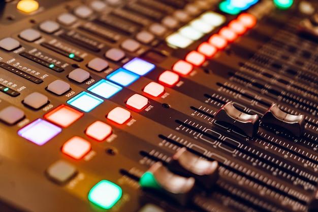 O console de mixagem para gravação com faders e botões brilhantes está instalado. fechar-se