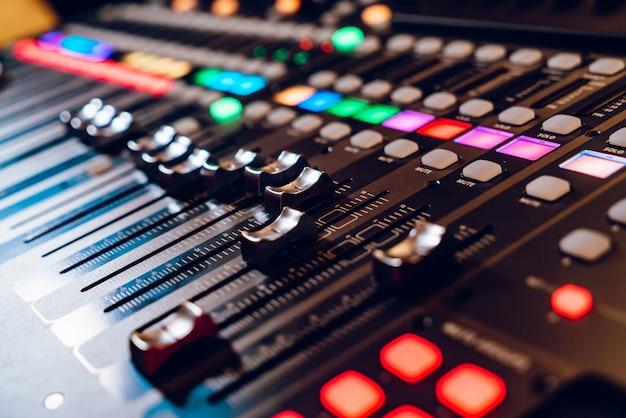 O console de mixagem profissional de concertos está equipado com faders de alta precisão e tempos longos.