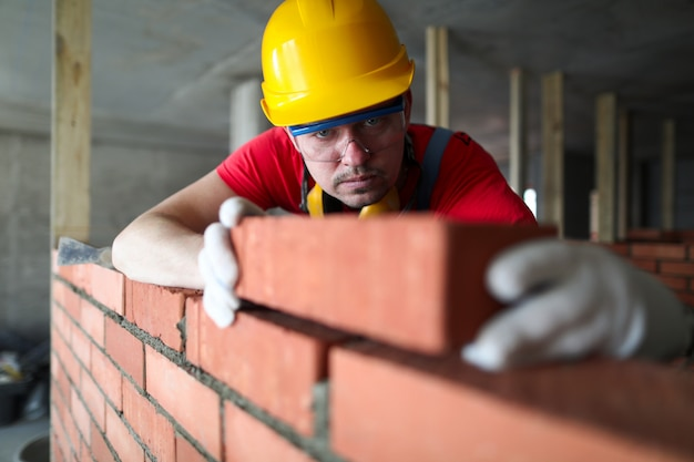 O construtor coloca cuidadosamente o tijolo vermelho na alvenaria