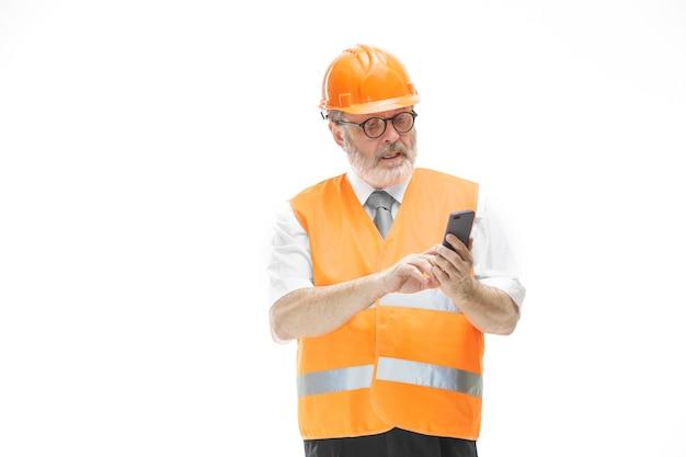 O construtor com um colete de construção e um capacete laranja falando ao telefone sobre alguma coisa. especialista em segurança, engenheiro, indústria, arquitetura, gerente, ocupação, empresário, conceito de trabalho
