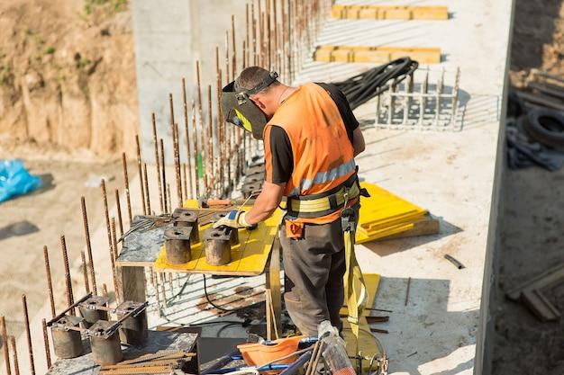 O construtor do soldador solda uma estrutura de metal em um canteiro de obras