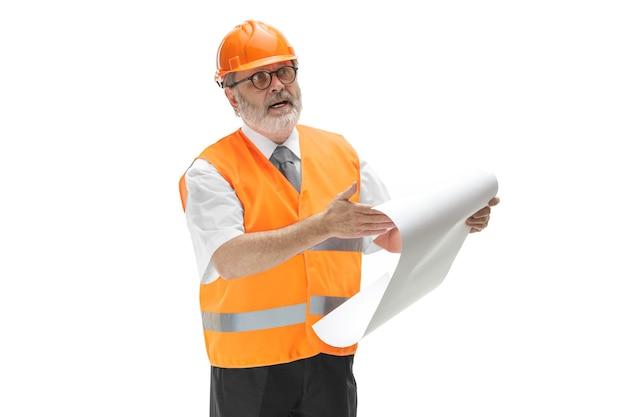 O construtor em capacete laranja isolado no branco