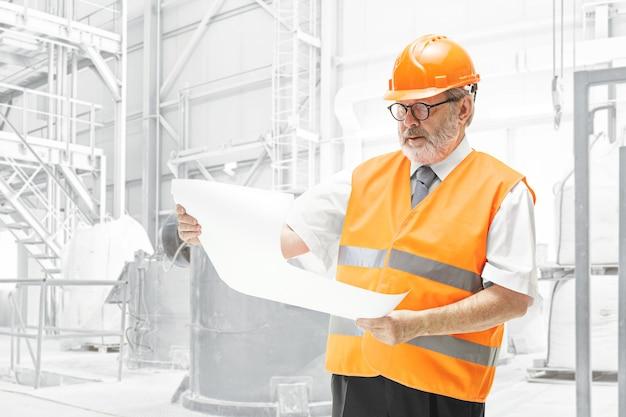 O construtor em um colete de construção e capacete laranja em pé na parede branca do estúdio