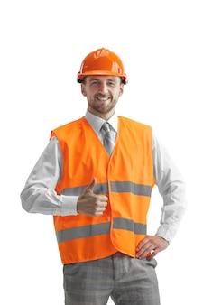 O construtor em um colete de construção e capacete laranja em pé na parede branca. especialista em segurança, engenheiro, indústria, arquitetura, gerente, ocupação, empresário, conceito de trabalho