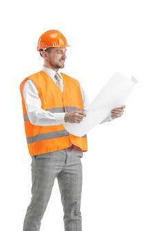 O construtor em um colete de construção e capacete laranja em pé no estúdio branco