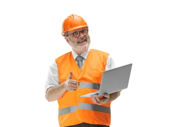 O construtor em um colete de construção e um capacete laranja com laptop