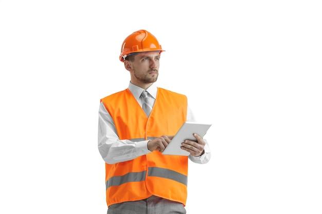 O construtor em um colete de construção e um capacete laranja com tablet. especialista em segurança, engenheiro, indústria, arquitetura, gerente, ocupação, empresário, conceito de trabalho
