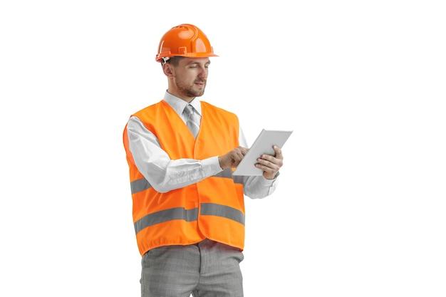 O construtor em um colete de construção e um capacete laranja com tablet.