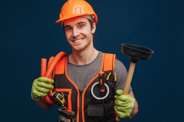 O construtor feliz está segurando o êmbolo e a trombeta