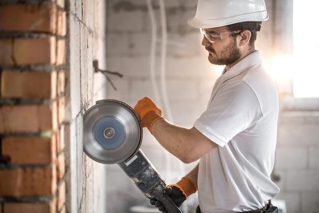 O construtor industrial trabalha com uma rebarbadora profissional para cortar tijolos e construir paredes interiores. eletricista.