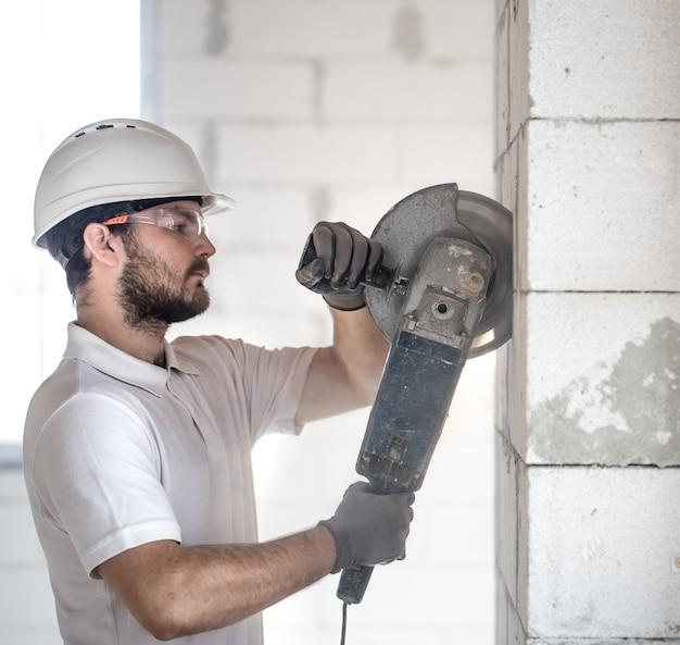 O construtor industrial trabalha com uma rebarbadora profissional para cortar tijolos e construir paredes internas