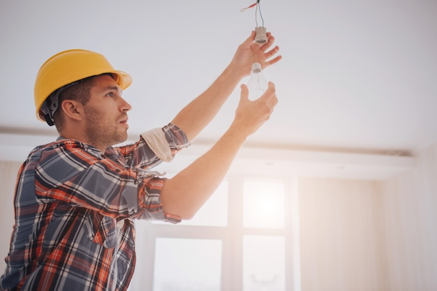 O construtor novo considerável em um capacete amarelo da construção está torcendo a ampola dentro. o homem está olhando para cima.