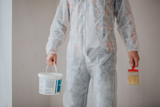 O construtor trabalha no canteiro de obras e mede o teto. trabalhador com balde e rolo de pintura perto da parede.