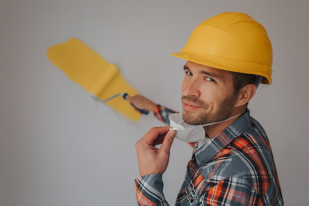 O construtor trabalha no canteiro de obras e mede o teto. um trabalhador de capacete laranja e rolo de pintura pinta a parede.