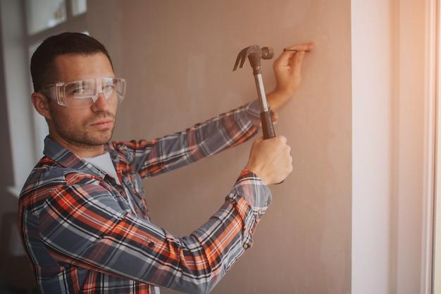 O construtor trabalha no canteiro de obras. trabalhador com balde e rolo de pintura perto da parede.