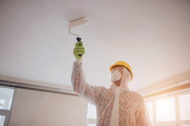 O construtor trabalha no canteiro de obras. trabalhador com um rolo de pintura. ele está vestindo um traje de proteção e máscara para um rosto
