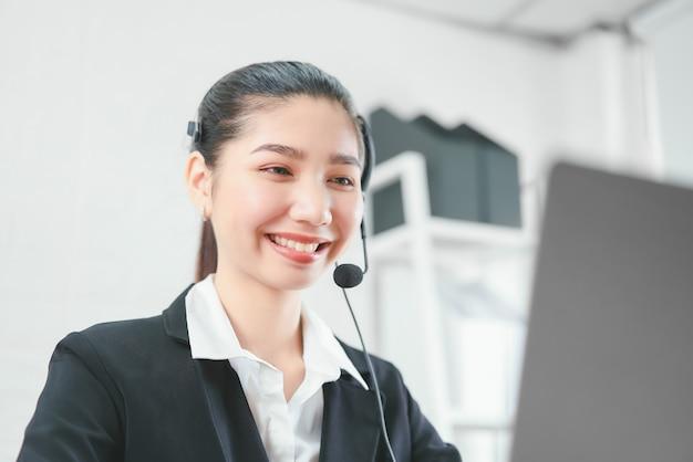 O consultor asiático de sorriso da mulher que veste auriculares do microfone do apoio ao cliente telefona ao operador no local de trabalho.