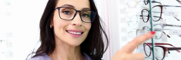 O consultor do gerente aponta para uma vitrine com ótica. salão para seleção de óculos e conceito de lentes