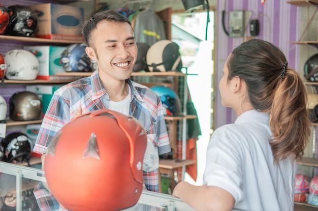 O consumidor conversa com os lojistas ao escolher um capacete em uma loja de capacetes