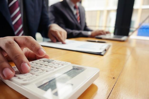 O contabilista verifica o negócio e economiza dinheiro acumulando moedas de ouro com calculadora. conceito de contabilidade