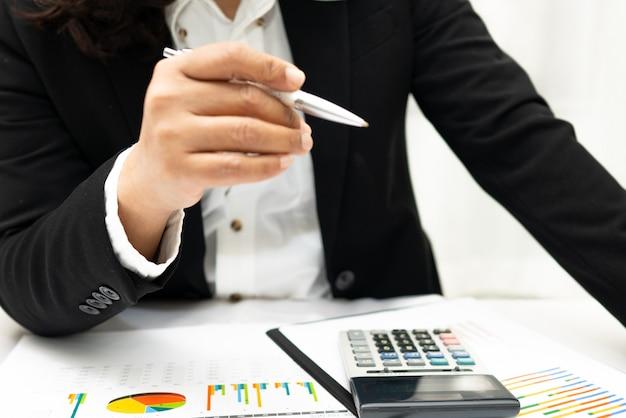 O contador asiático que trabalha e que analisa relatórios financeiros projeta a contabilidade com gráfico.
