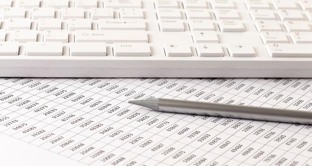 O contador de negócios trabalha com impostos e teclado na vista superior da mesa de escritório branca