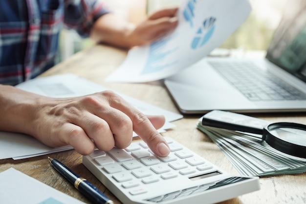 O contador está pressionando a calculadora para calcular verificar a precisão do orçamento de investimento