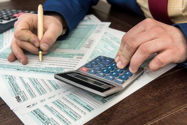 O contador preenche o formulário de imposto. documento de finanças contábil do empresário. papelada, hora do imposto