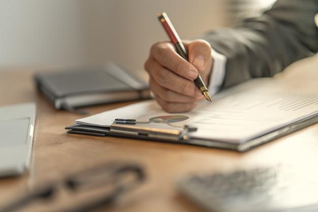 O contador que verifica documentos sobre gráfico e carta relacionando com relatórios financeiros e contabilidade de imposto da companhia