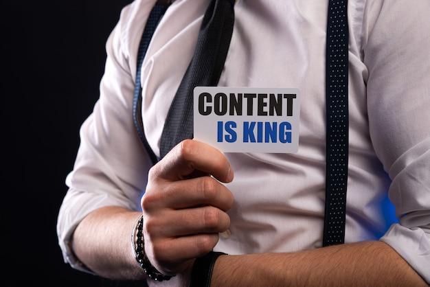 O conteúdo é as palavras do rei no cartão branco na mão.