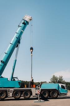 O contrapeso é instalado por um trabalhador irreconhecível em uma grande ponte rolante azul e está preparado para trabalhar em um local próximo a um grande edifício moderno.