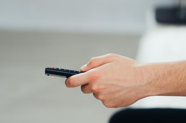 O controle remoto da tv na mão, em um ambiente caseiro aconchegante, em frente à tv