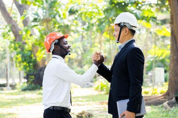 O coordenador asiático e africano do arquiteto agita as mãos com sorriso na natureza verde.