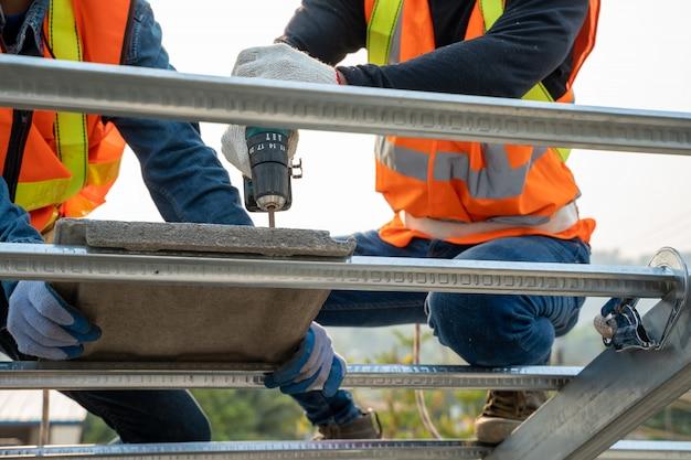 O coordenador de construção veste o carpinteiro uniforme da inspeção da segurança que trabalha na estrutura de telhado da construção no canteiro de obras.