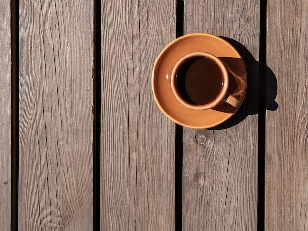 O copo de café marrom na mesa de madeira, dia de sol, sombra natural,