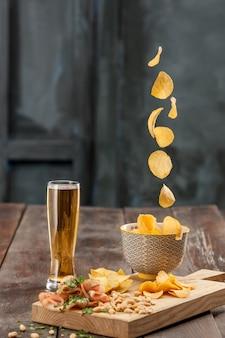 O copo de cerveja e batata frita, pistache isolado em um branco