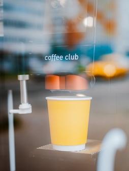 O copo de papel amarelo é uma bebida pela manhã através do vidro na rodovia.