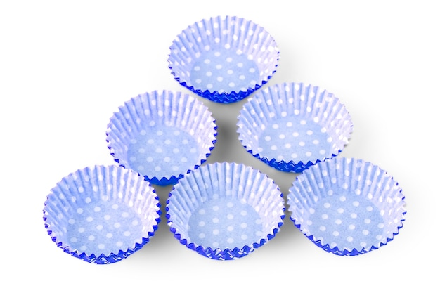 O copo de papel de bolinhas azuis isolado sobre o fundo branco