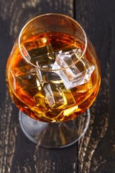 O copo de uísque com cubos de gelo serviu em pranchas de madeira. bancada vintage com destaque e um copo de licor